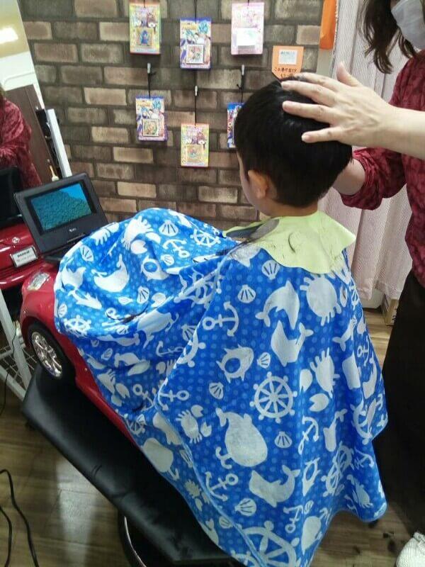 息子が車型のカット椅子に座り、DVDを見てる内に散髪している写真。