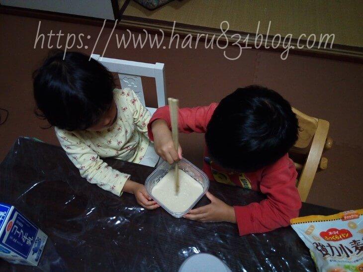 子どもたちがパンの材料を混ぜてる写真